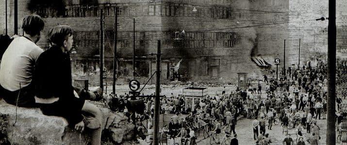 Jungen sitzen auf einer Mauer und schauen protestierenden Arbeitern zu